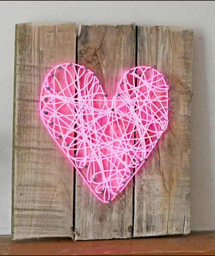 string art on a wooden background made with a neon string that lights up