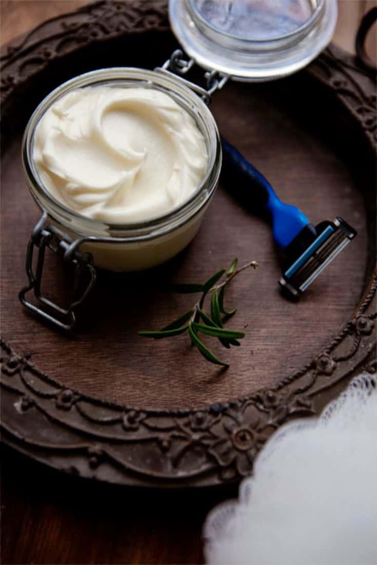 a jar with shaving cream next to a razor