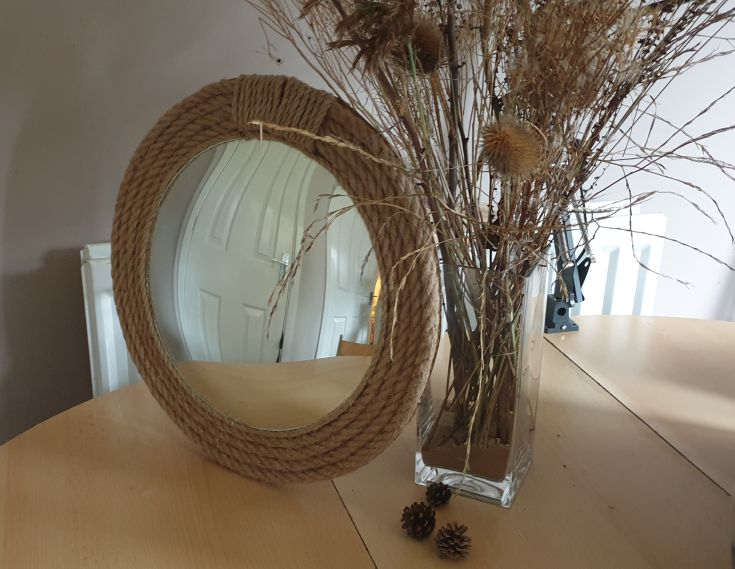 diy rope mirror frame next to a vase with dry grass